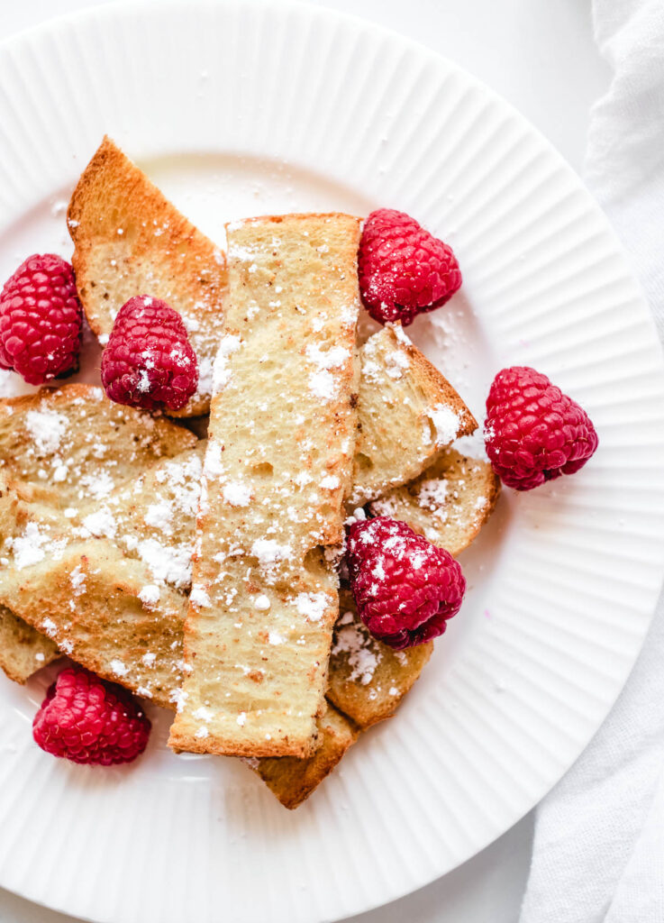 close up of vegan French toast sticks layered on top of one another topped with powdered sugar and raspberries