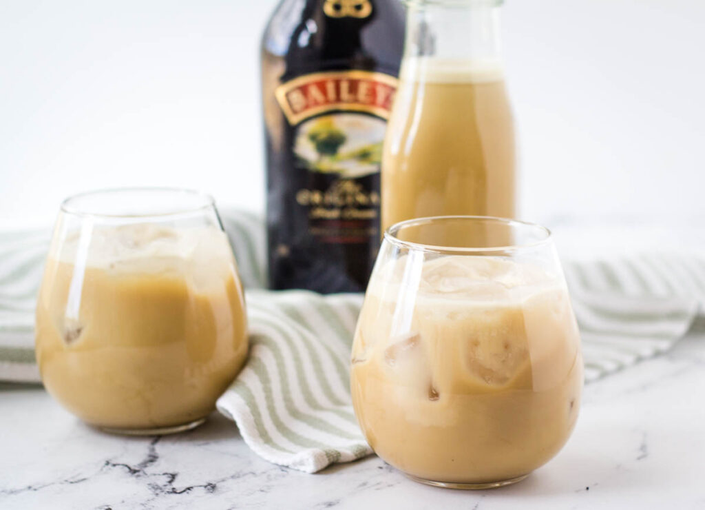 vegan Irish cream in two stemless wine glasses with Bailey's bottle in the background