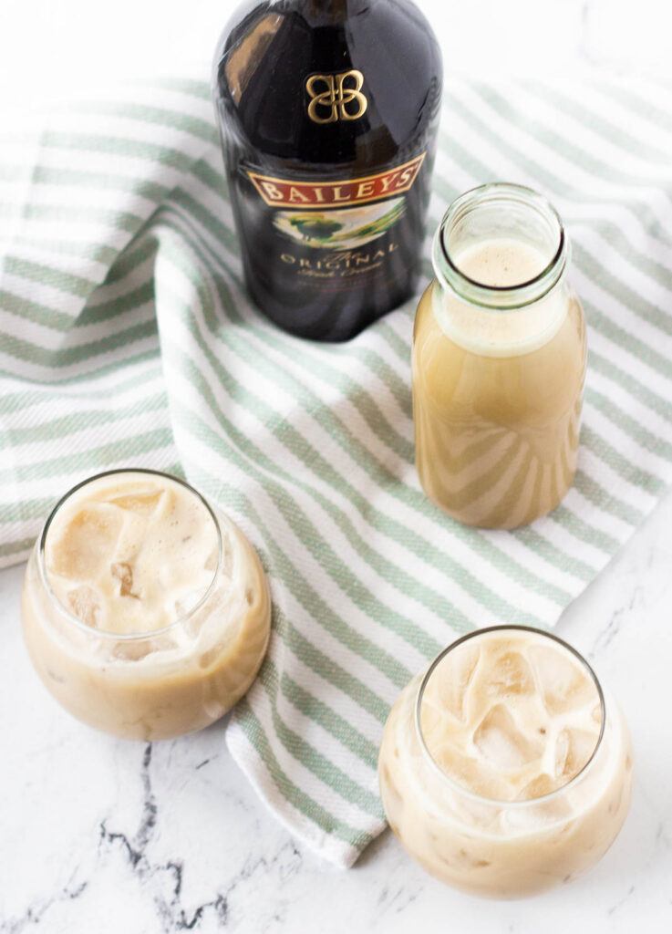 overhead of vegan Irish cream in stemless wine glasses with Bailey's bottle in the background