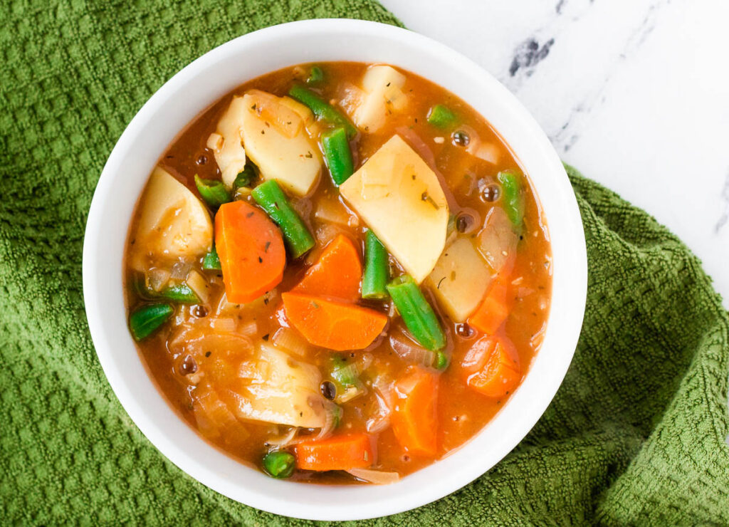 potato and carrot stew with green beans in white bowl