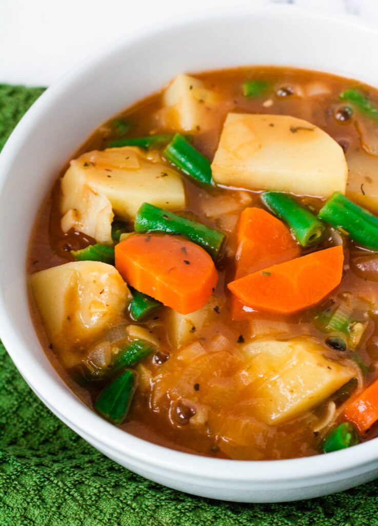 vegan Irish stew in white bowl with carrots, potatoes, and green beans