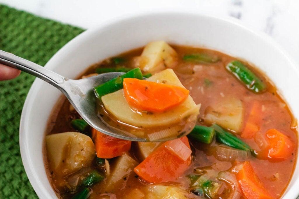 spoonful of vegan Irish stew held over white bowl
