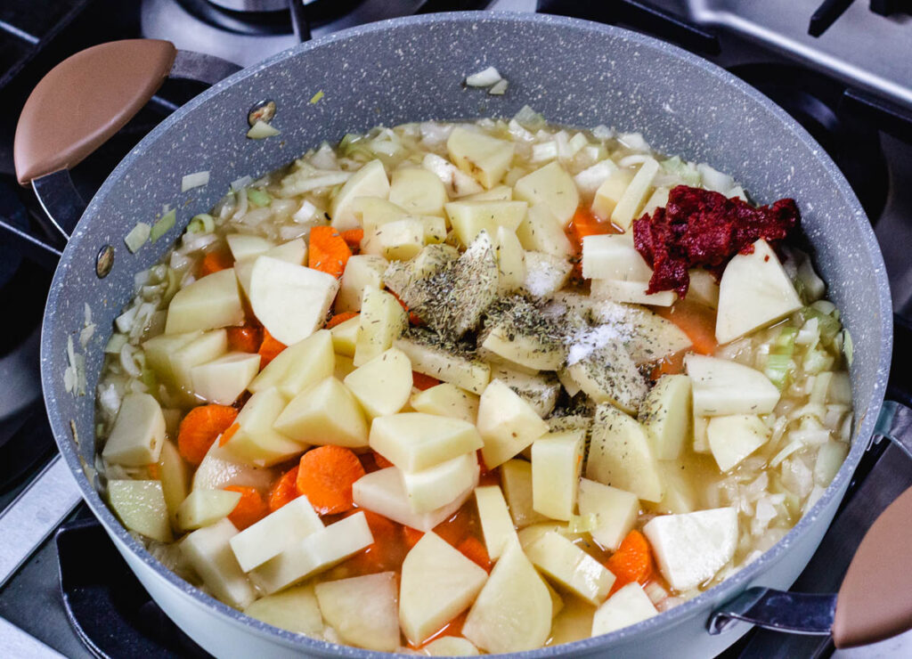 carrots, potatoes, spices, and tomato paste in pot of onions and vegetable stock