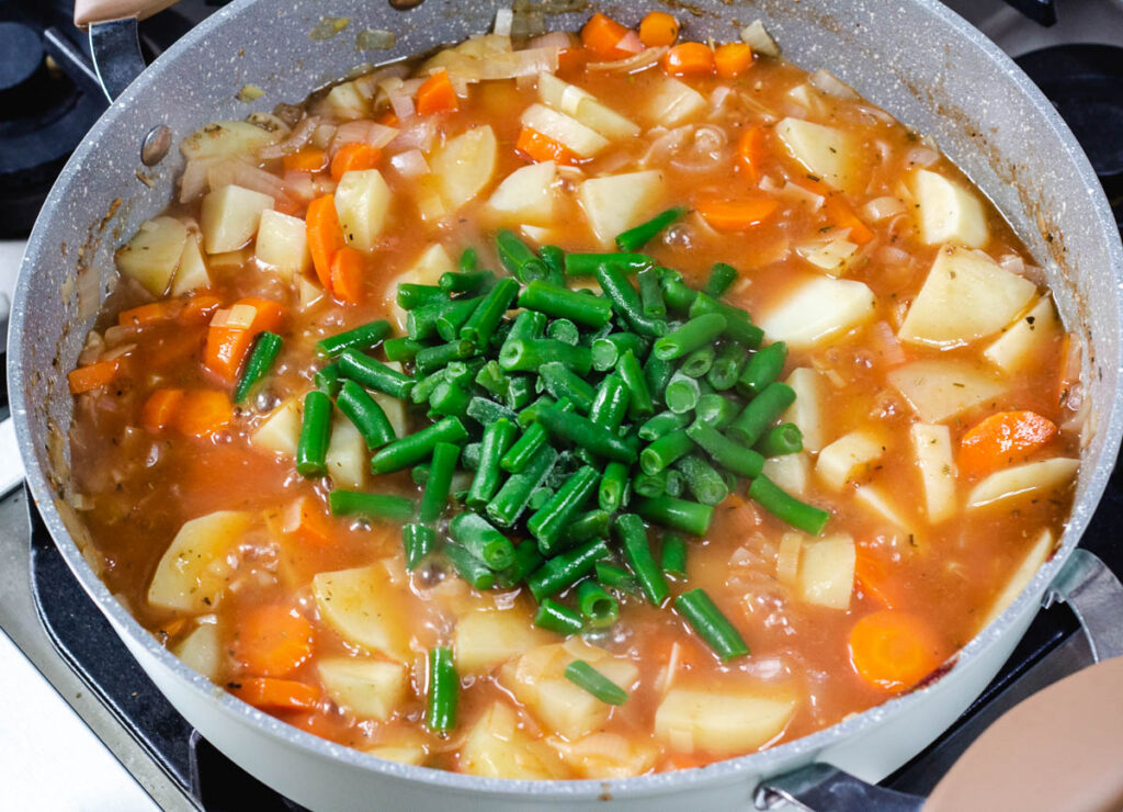 vegan Irish stew in pot with added green beans