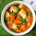 vegan Irish stew in white bowl over green kitchen towel