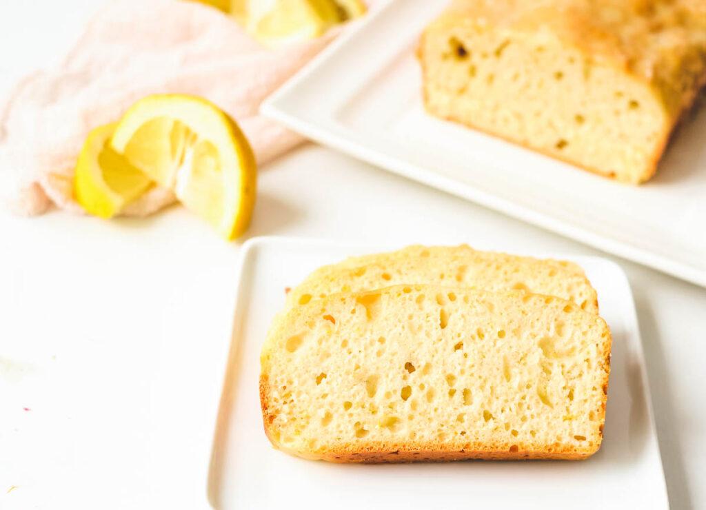 vegan lemon loaf slices on white plate with lemon loaf in the background and slices of lemon