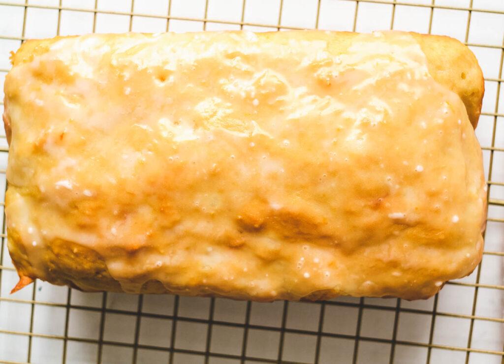 lemon loaf topped with glaze on cooling rack