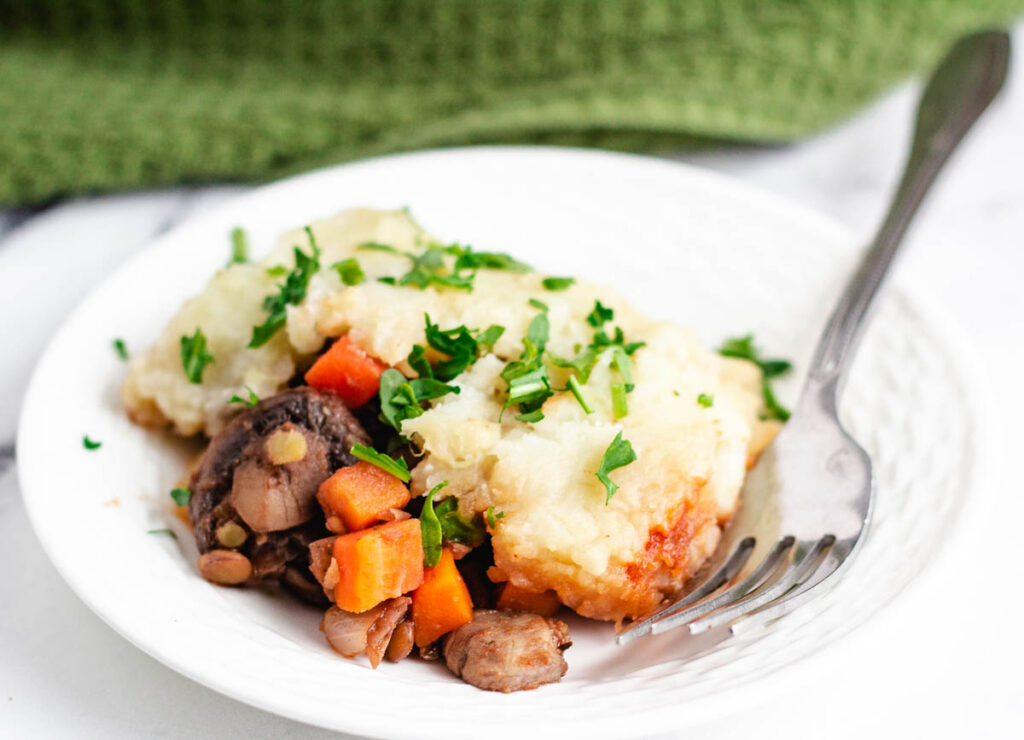 lentil and mushrooms topped with mashed potatoes and chopped herbs on white serving plate with fork