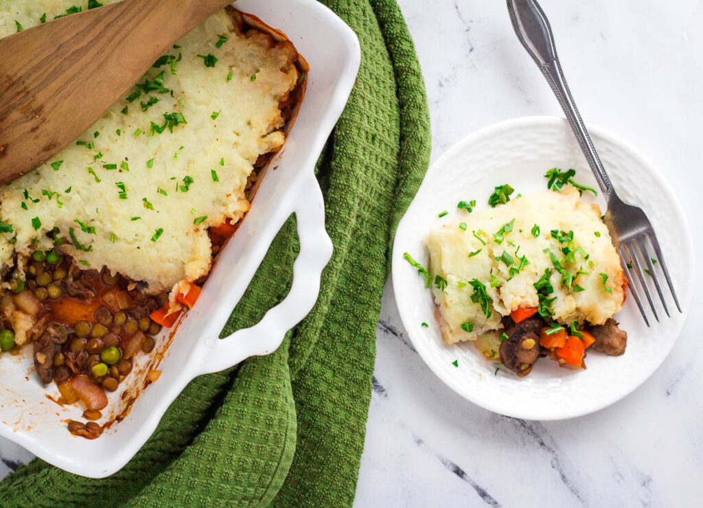 vegan lentil shepherd's pie in casserole dish with serving taken out, on white plate with fork