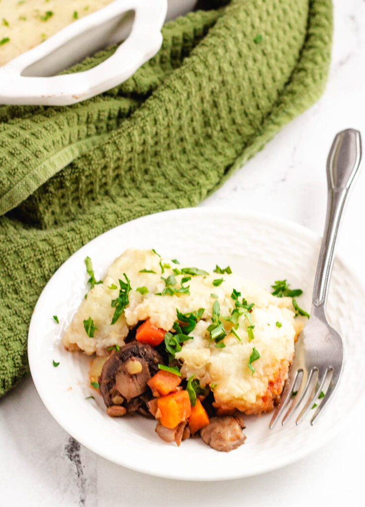 lentil shepherd's pie with mushrooms and carrots on white plate with fork