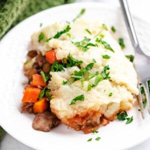 vegan lentil shepherd's pie serving on white plate with fork