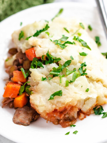 vegan lentil shepherd's pie serving on white plate with fork