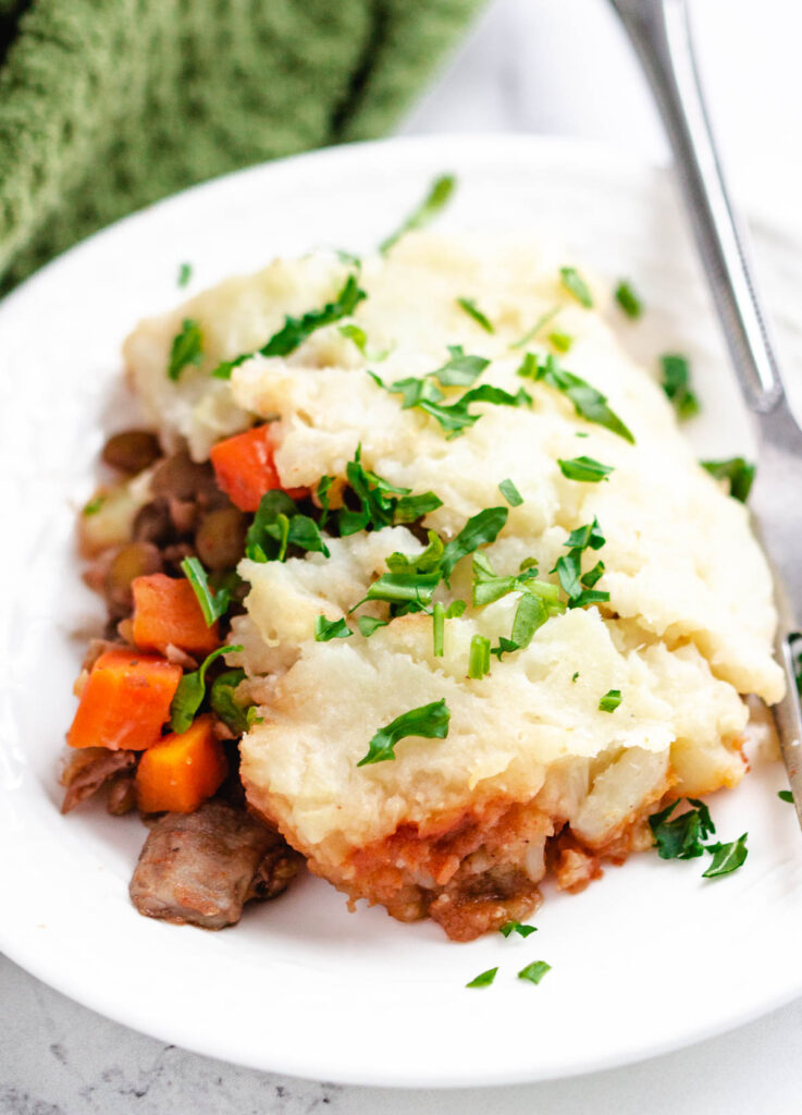 serving of vegan lentil shepherd's pie on white plate topped with fresh herbs