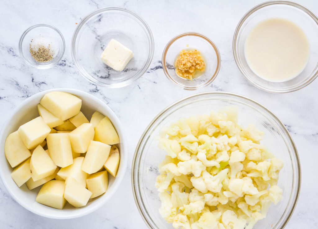healthy mashed potato ingredients: cubed russet potato, cauliflower florets, soy milk, garlic, vegan butter, salt, and pepper