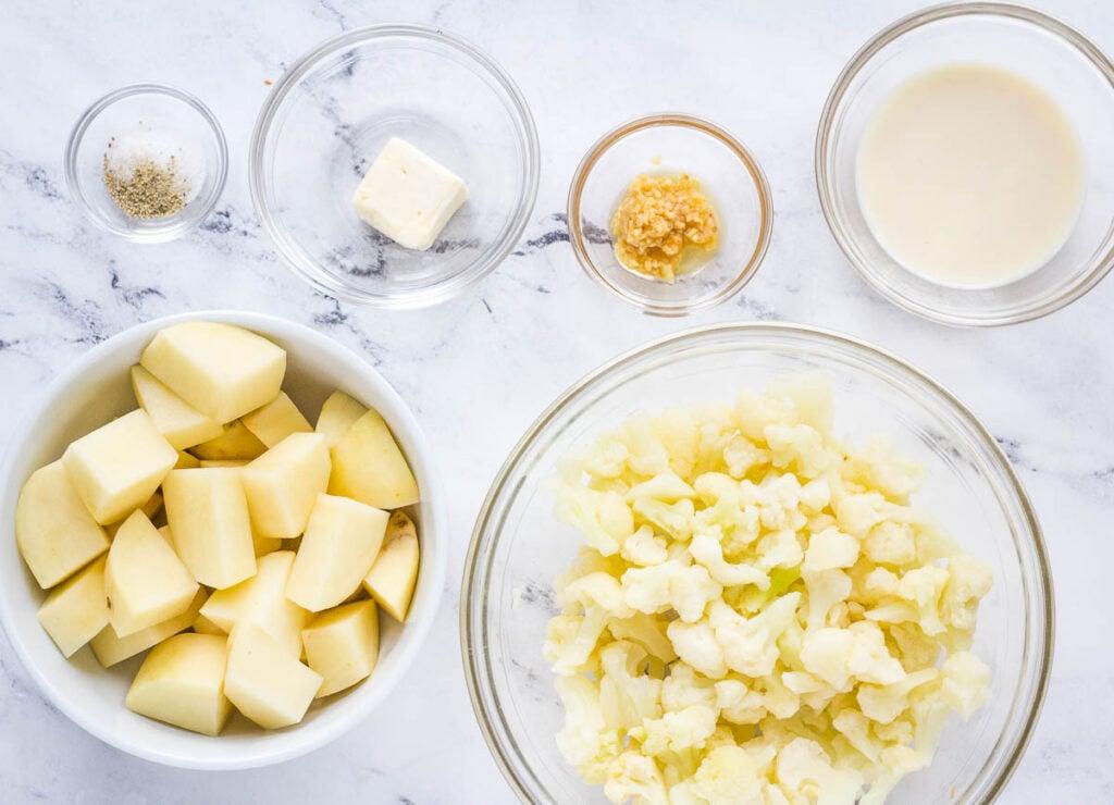 healthy mashed potato ingredients: cubed russet potato, cauliflower florets, soy milk, garlic, vegan butter, salt, and pepper