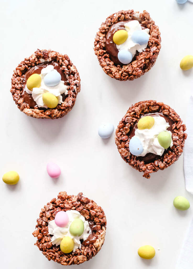 birds nest cookies with chocolate rice cereal nest, gilled with chocolate ganache and topped with whipped cream and candy eggs