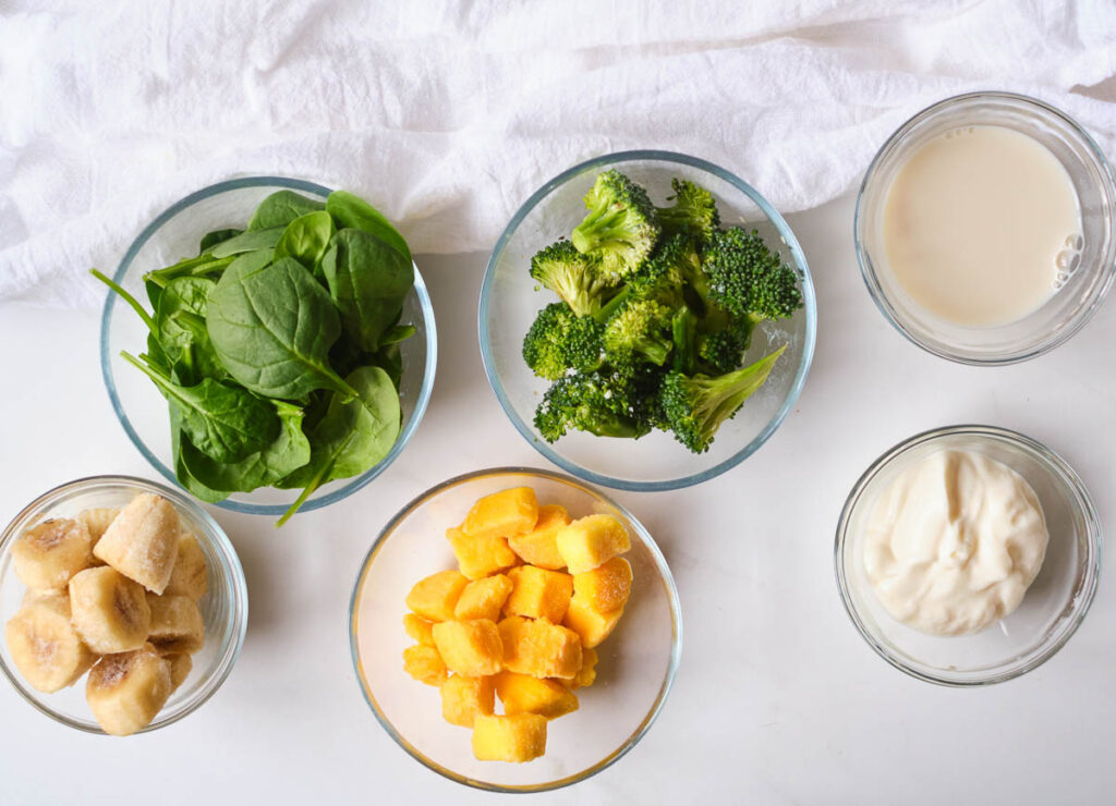 spinach, broccoli florets, frozen banana, frozen mango, dairy-free yogurt, and almond milk in glass bowls
