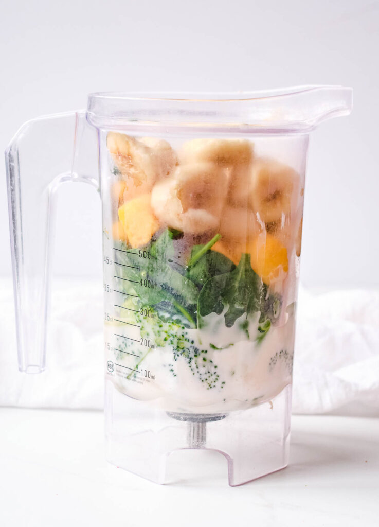 pre blended smoothie ingredients: milk on the bottom, followed by broccoli and spinach, topped with frozen mango and frozen banana.