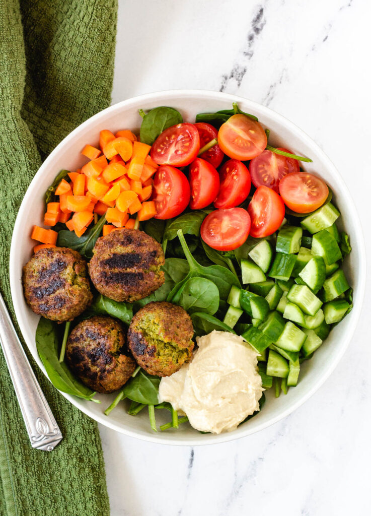 overhead of falafel plate with spinach, cucumber, tomatoes, and carrots