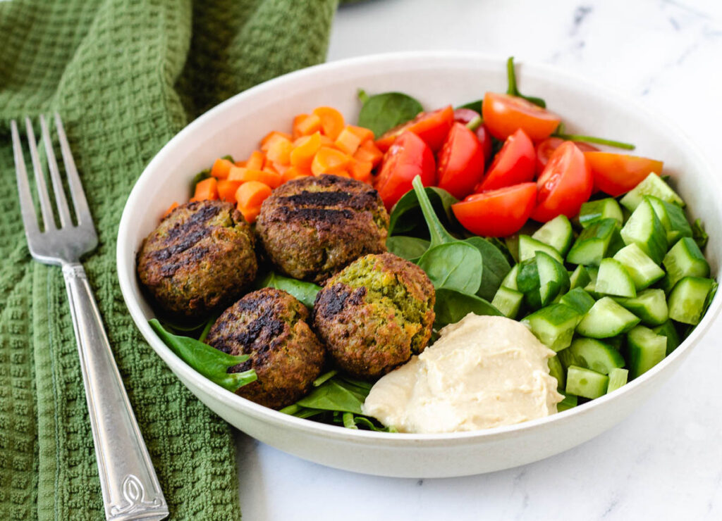 falafel plate with spinach, hummus, cucumbers, tomatoes, and carrots