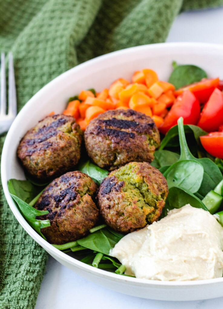 falafel balls on bed of spinach served with hummus