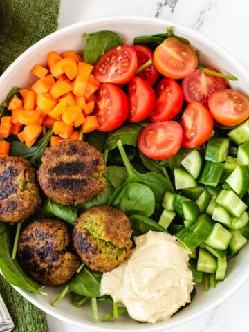 falafel plate with hummus, cucumber, tomatoes, carrots, and spinach