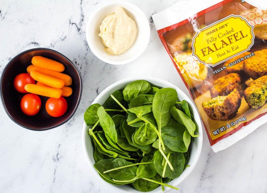 Trader Joe's falafel bag, bowl of spinach, hummus, tomatoes, and carrots