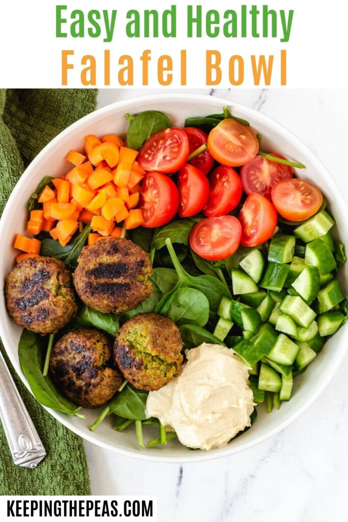 spinach topped with falafel, hummus, cucumbers, tomatoes, and carrots