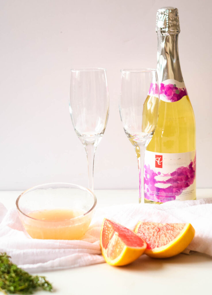 bottle of champagne, two champagne flutes, wedge of grapefruit, grapefruit juice in bowl, and fresh thyme