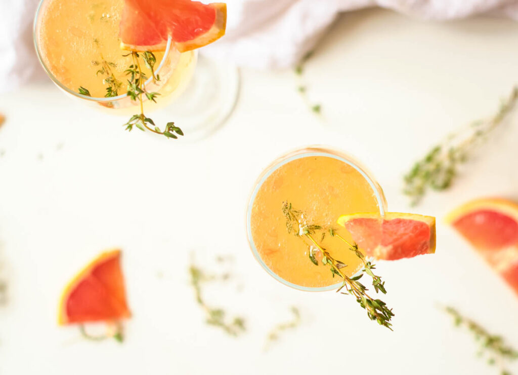 overhead of top of champagne flute filled with a mimosa and topped with thyme and a wedge of grapefruit