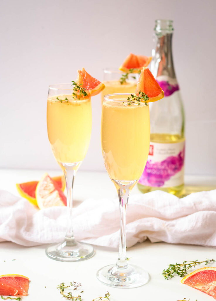 grapefruit mimosas in champagne flutes garnished with fresh thyme and wedge of grapefruit