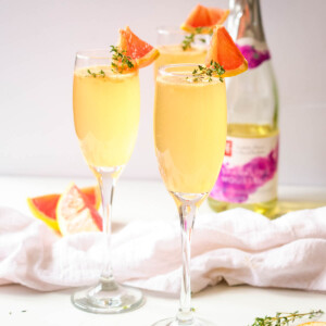 grapefruit mimosas in champagne flutes with thyme and grapefruit wedge