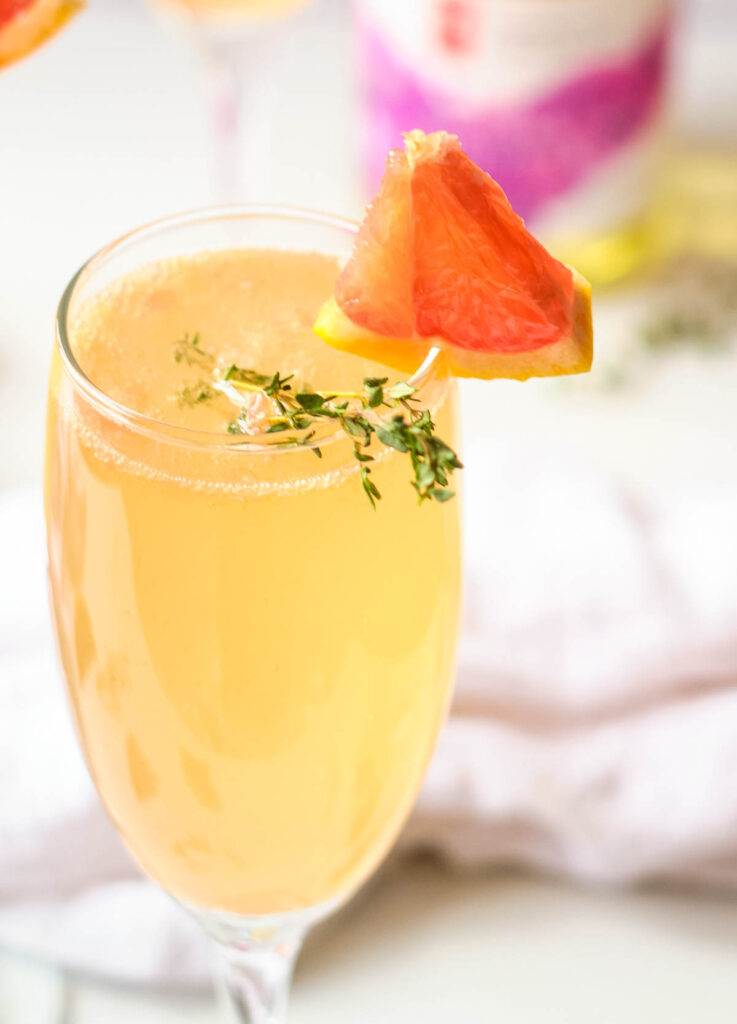 grapefruit mimosa in champagne flutes garnished with fresh thyme and wedge of grapefruit