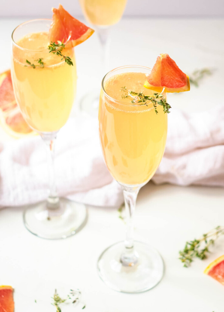 mother's day brunch mimosas in champagne flutes garnished with fresh thyme and wedge of grapefruit