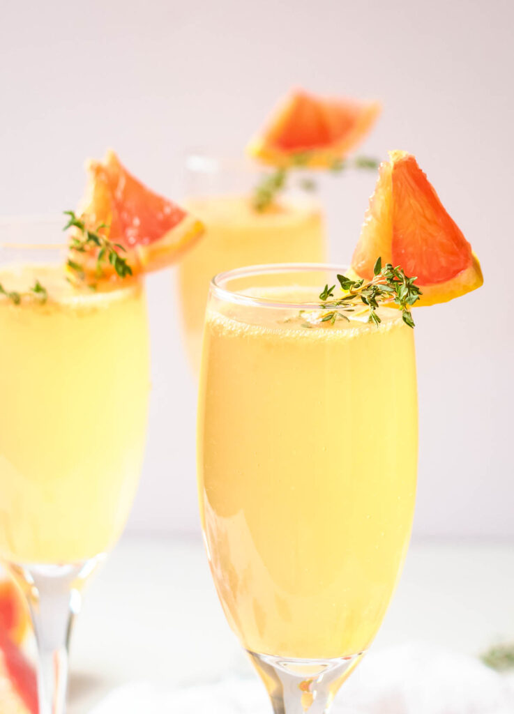 Easter mimosas in champagne flutes garnished with fresh thyme and wedge of grapefruit