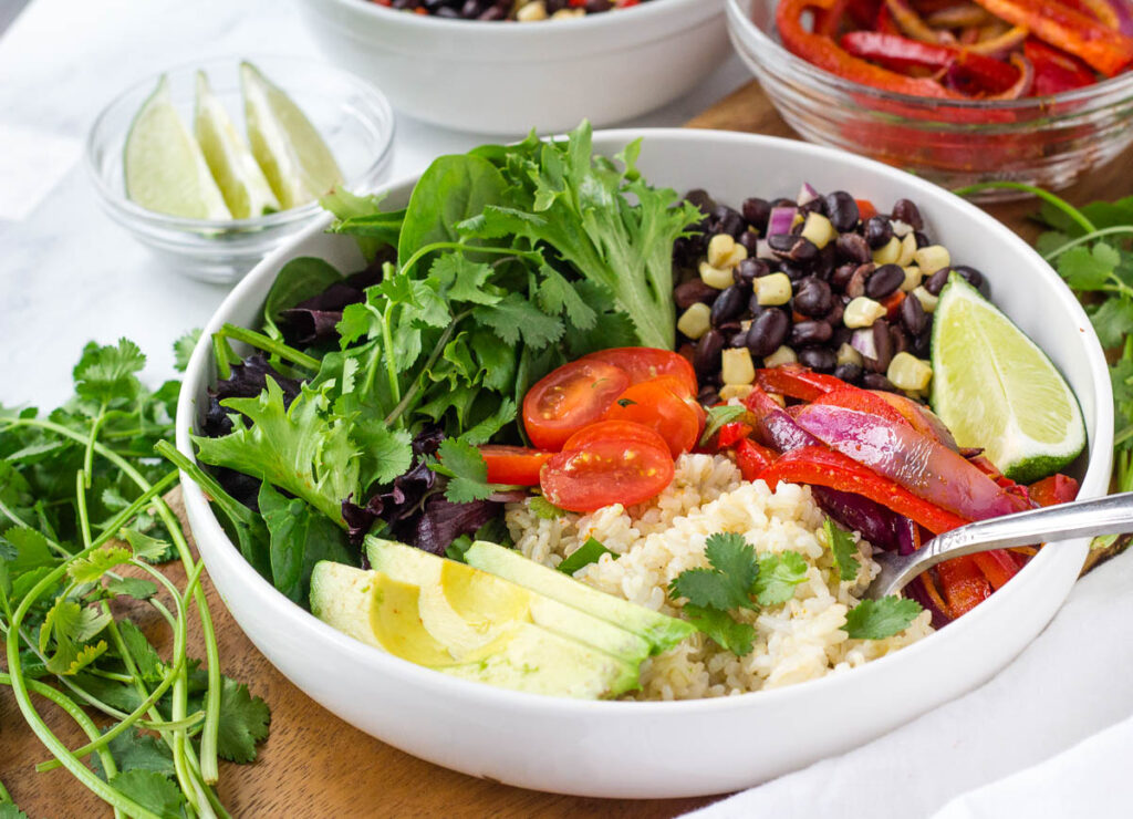 healthy burrito bowl with brown rice, fajita vegetables, black beans, and greens