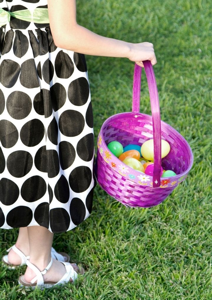 little girl in polka dot dress holding purpose Easter basket filled with plastic eggs