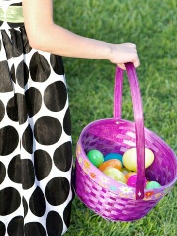 little girl in polka dot dress holding purple Easter basket filled with plastic eggs