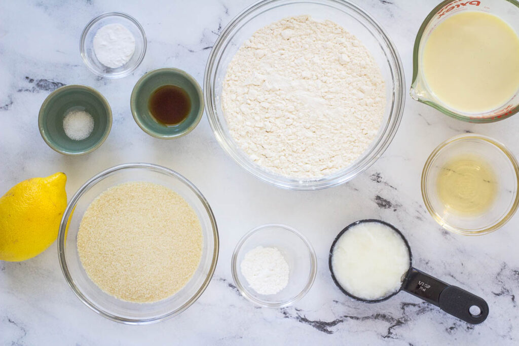 ingredients for vegan lemon cupcakes: baking powder, baking soda, sugar, salt, vanilla extract, flour, coconut oil, apple cider vinegar, soy milk