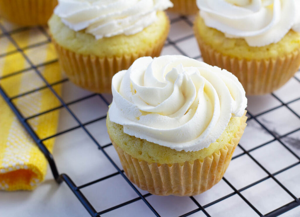 vegan lemon cupcake frosted with buttercream on cooling rack