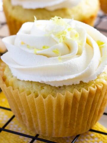 vegan lemon cupcake with lemon buttercream frosting, topped with lemon zest