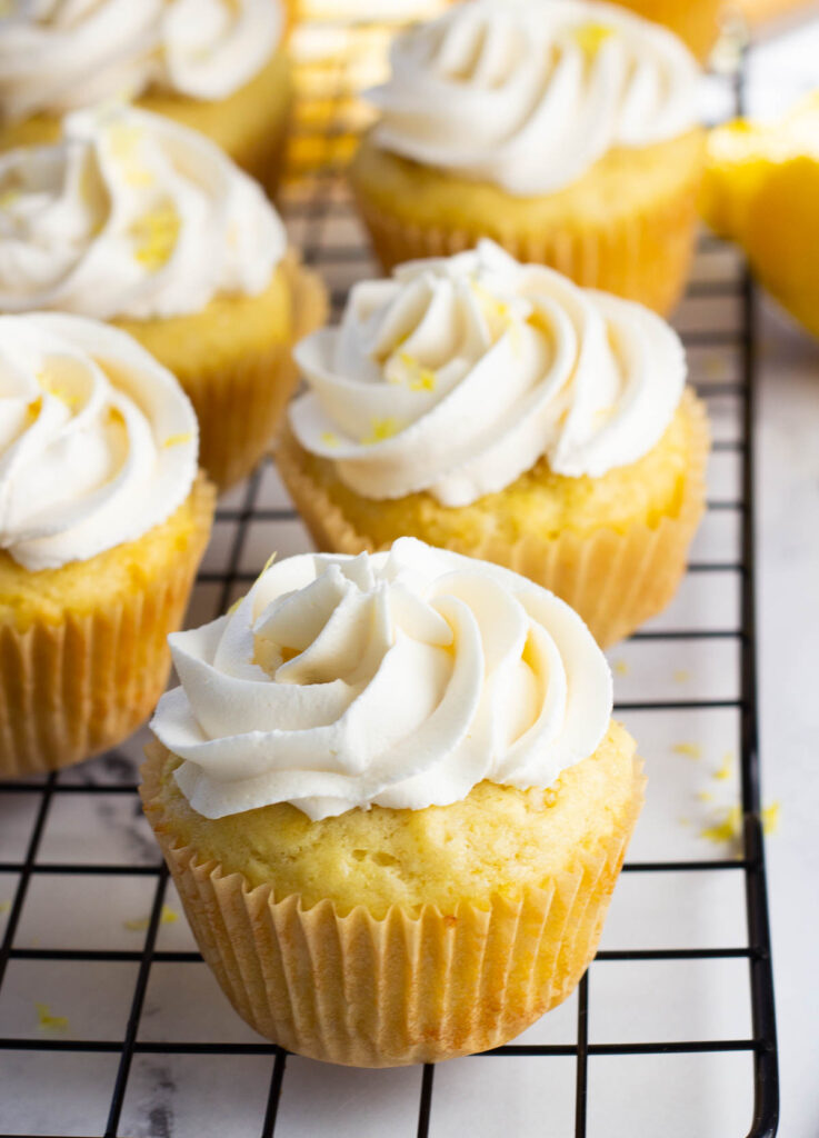 vegan lemon cupcakes on cooling rack, topped with buttercream frosting and lemon zest