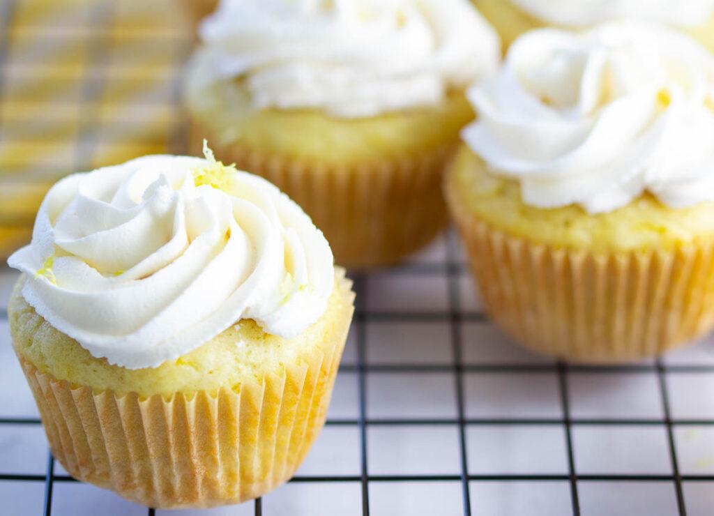 vegan lemon cupcakes with buttercream frosting and lemon zest on cooling rack