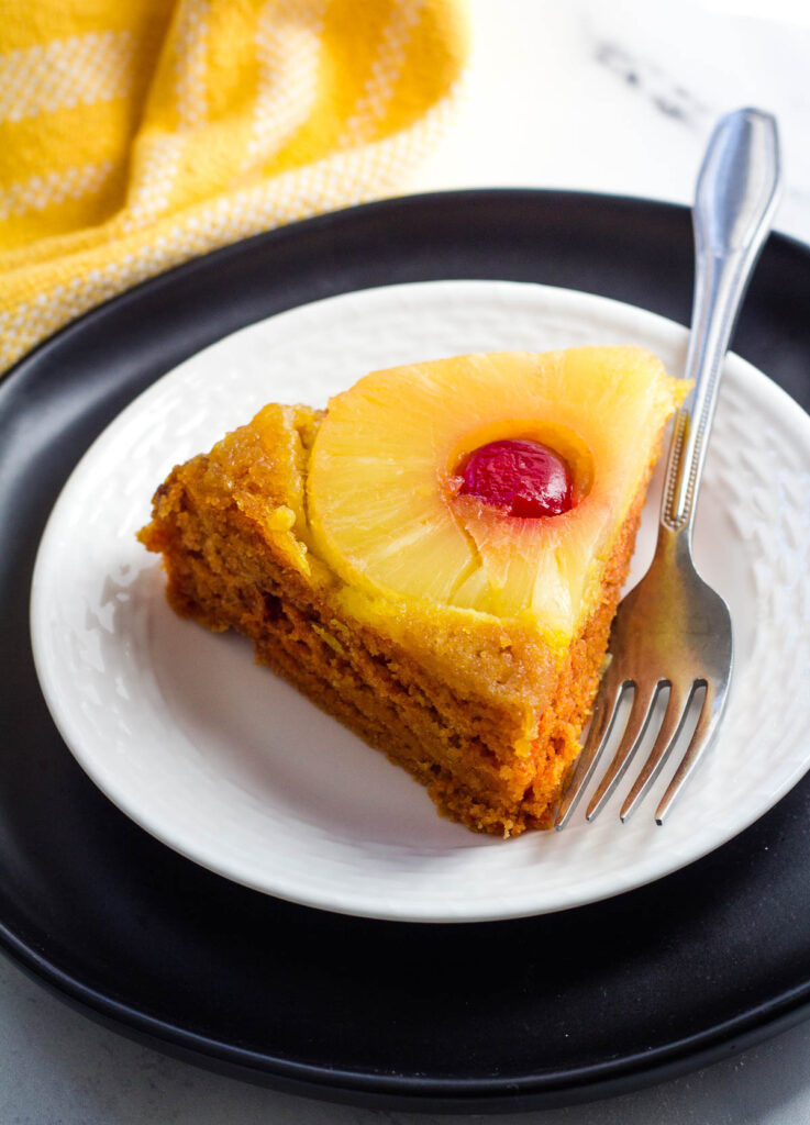 slice of vegan pineapple upside down cake on plate with fork