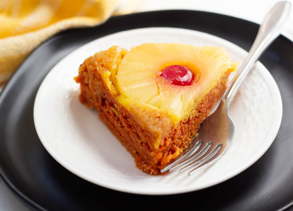 slice of vegan pineapple upside down cake on white and black plate with fork