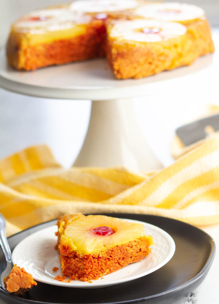 pineapple upside down cake slice on plate with cake and cake stand in the background