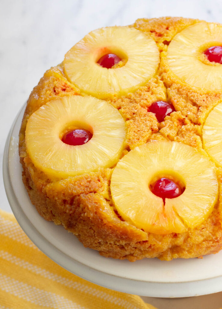 vegan pineapple upside down cake with pineapple rings and maraschino cherries