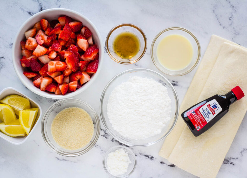ingredients for vegan pop tarts: puff pastry sheets, vanill extract, corn starch, powdered sugar, plant milk, maple syrup strawberries, sugar, and lemon slices