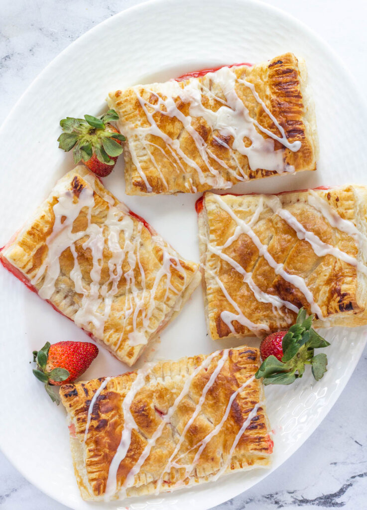 4 vegan hand pies on white serving plate with strawberries