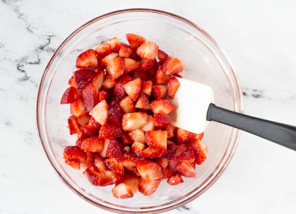 sliced strawberries in glass bowl